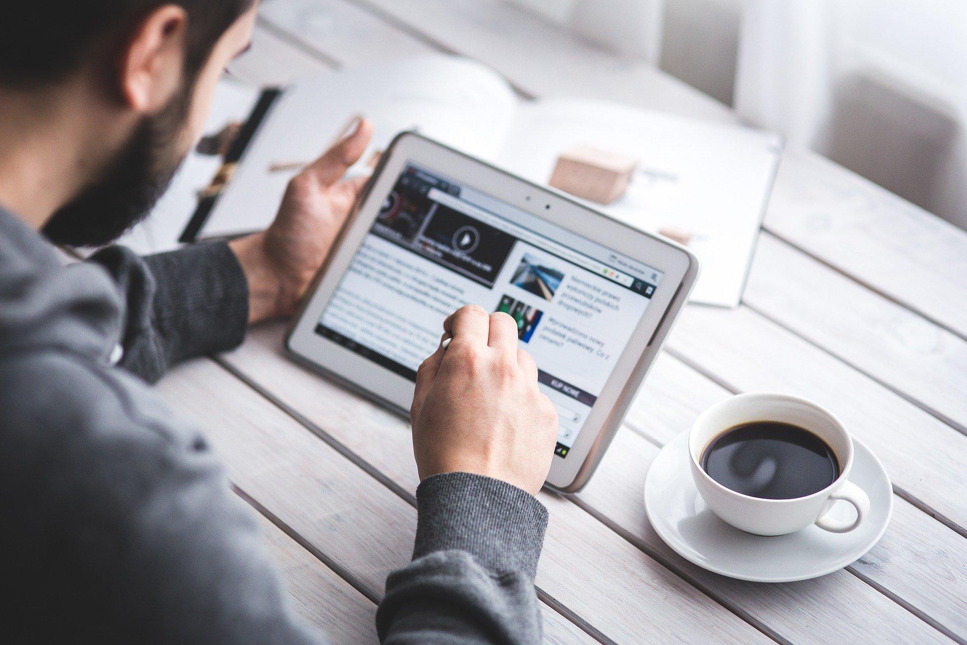 Mand læser blog på tablet