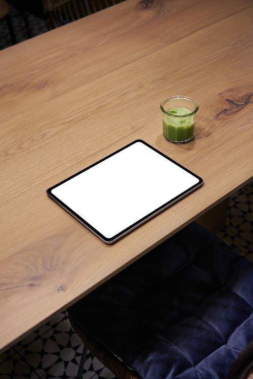 nyd en grøn smoothie ved bordet efter træning og udstrækning